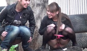 Two girlfriends smiling as they piss next to a huge tree