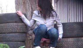 Striped panties teen pissing next to stacked tires, outdoors