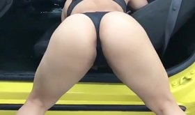 Crystina Rossi shows off her ass and shakes it next to a car