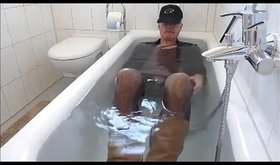 Mature guy lying in the bathtub while masturbating
