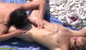 Dark-haired mature girlfriend blows her man on a beach